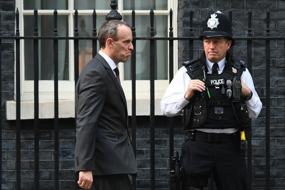 Dominic Raab walks past a policeman outside Downing Street