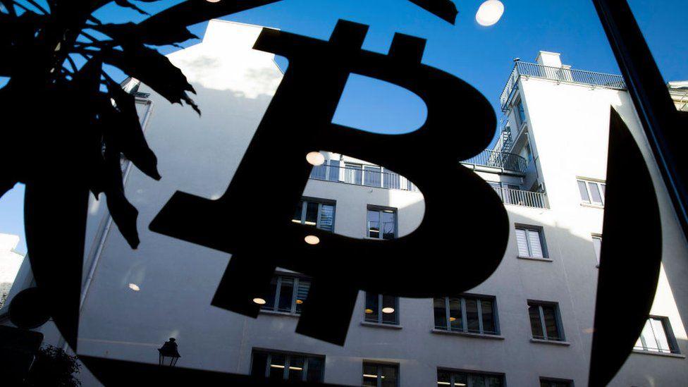 A bitcoin logo on a window at La Maison du Bitcoin in Paris