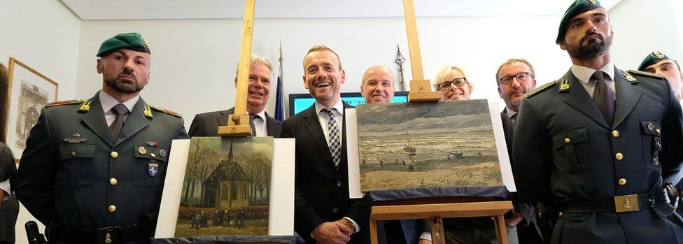 """Axel Ruger (C), Director of the Van Gogh museum poses next to Congregation Leaving the Reformed Church in Nuenen"""" (L) and """"The Beach At Scheveningen During A Storm"""" (R)"""