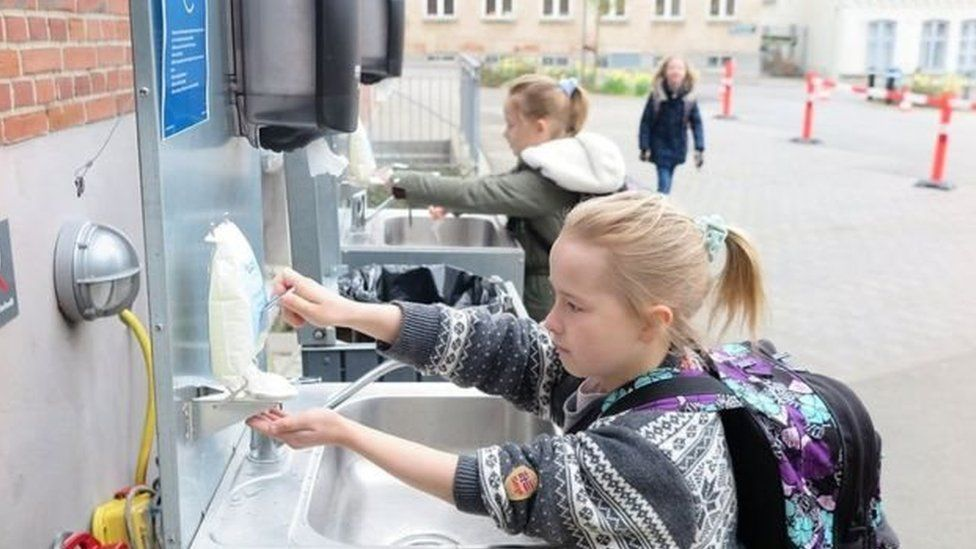 children washing hands at outdoor sinks