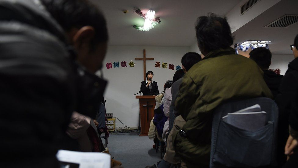 A photo taken on December 24, 2014 shows a pastor of an underground church conducting a Christmas Eve service at an apartment in Beijing