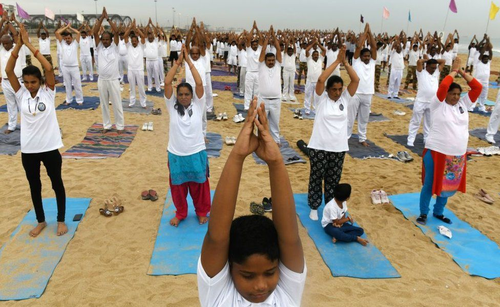 Indian children along with yoga enthusiasts take part in a yoga session to mark International Yoga Day on a beach in Chennai on June 21, 2019. - Indian Prime Minister Narendra Modi led the way for International Yoga Day on June 21, performing sun salutations and other flexible feats in a mass session with an estimated 30,000 other devotees of the discipline.