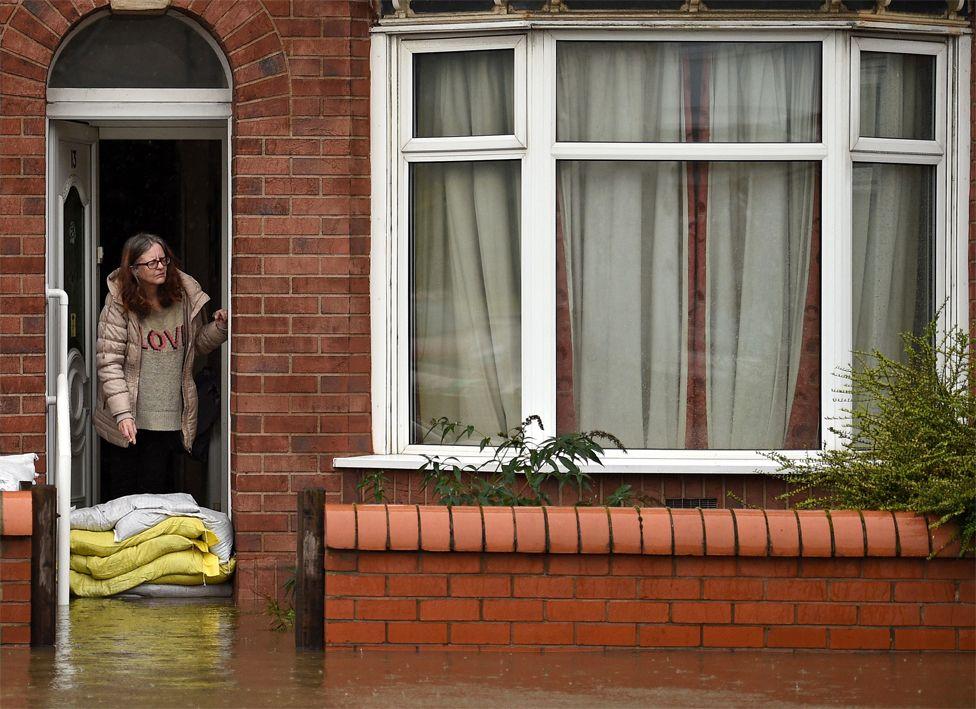Një grua qëndron me çanta rërë jashtë shtëpisë së saj