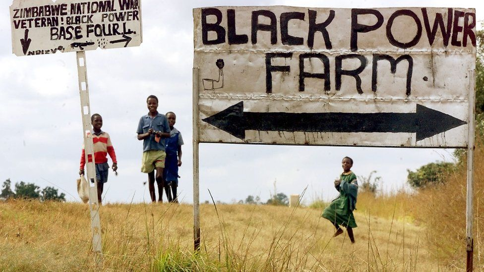 Schoolchildren pass the entrance to an occupied farm outside Harare, Zimbabwe - 2000