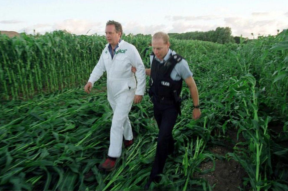 Greenpeace executive director Lord Peter Melchett being led away by a policeman during a protest by enviromental campaigners against genetically modified crops at Lyng, near Norwich, Norfolk