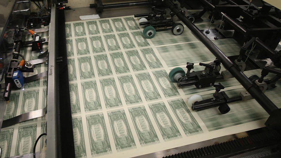 Dollar bills roll off a printing press.