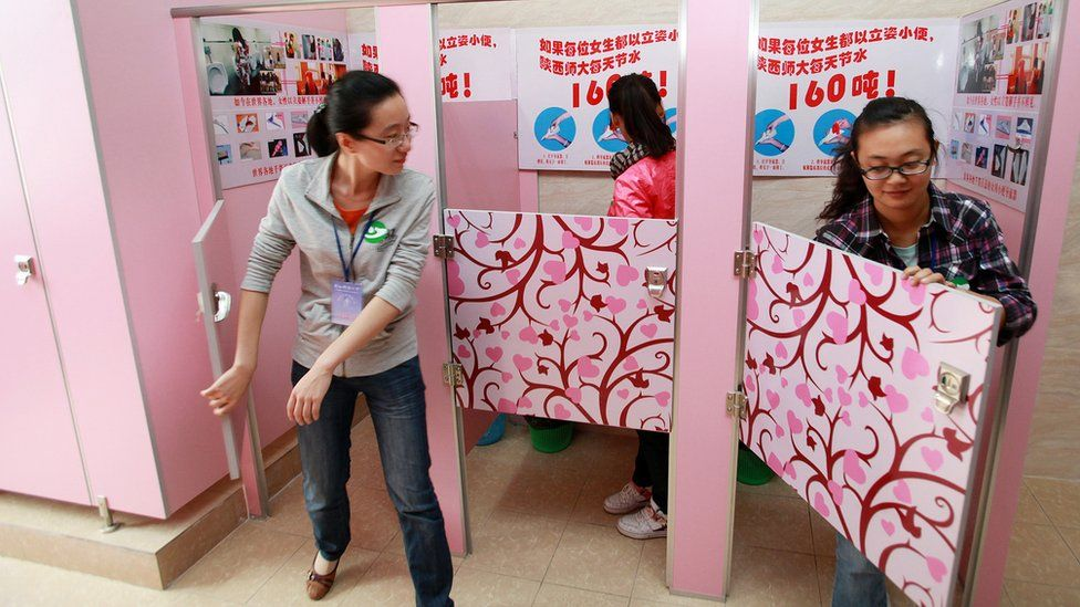 Women students using pink cubicles containing urinals with a sign instructing women how to urinate standing, at a toilet in Shanxi Normal University in Xian, in northwest China's Shanxi province (September 26, 2010)