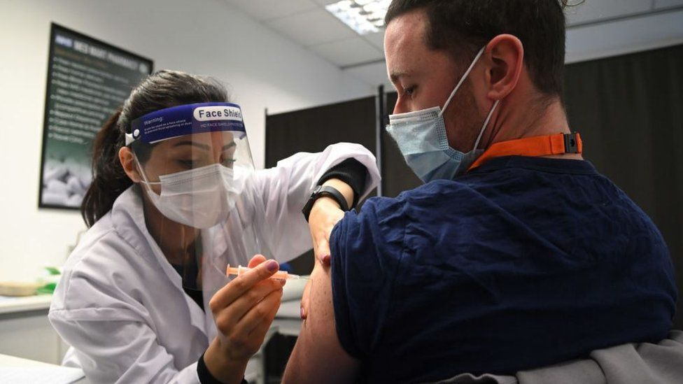 A care worker being vaccinated at a pharmacy in Borehamwood