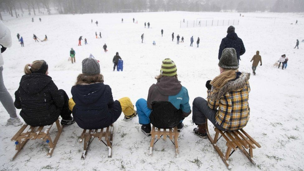 People enjoy a sled ride in the snow on a hill in Rotterdam