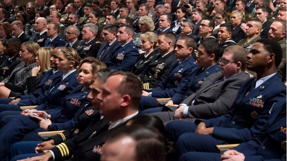 Rows of military members sit in audience of Donald Trump speech.