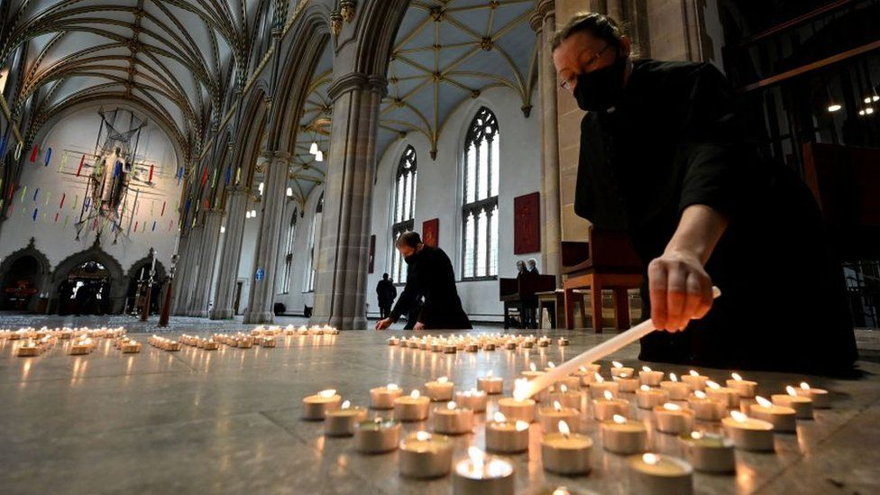 A verger lights one of 4,161 candles representing each death from Covid-19 in Lancashire county at Blackburn Cathedral