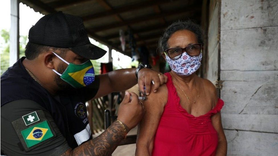 """A health worker of the Indigenous Special Sanitary District of Manaus administers Sinovac""""s CoronaVac coronavirus disease (COVID-19) vaccine to an Indigenous person at Sao Jose Village in the Indigenous land Rio Urubu from the ethnicity Mura in the Urubu river banks in Itacoatiara, Amazonas state, Brazil, February 13, 2021."""