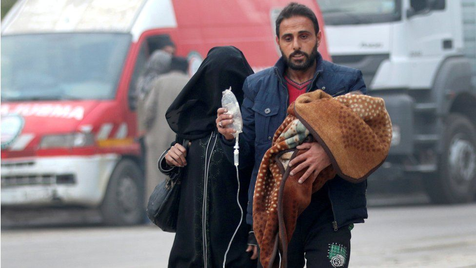 A man carries a child with an IV drip as he flees deeper into the remaining rebel-held areas of Aleppo, Syria December 12, 2016