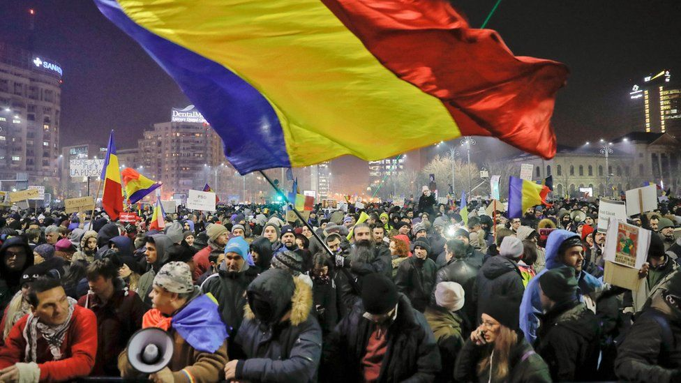 A man waves a large Romanian flag during a protest joined by tens of thousands against a government decree that dilutes what qualifies as corruption, in Bucharest, Romania