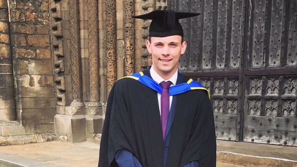 Rhys Dickinson in mortar board and gown