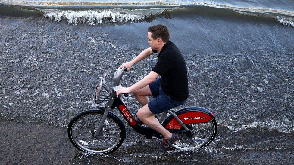 Man riding bike in Putney during high tide