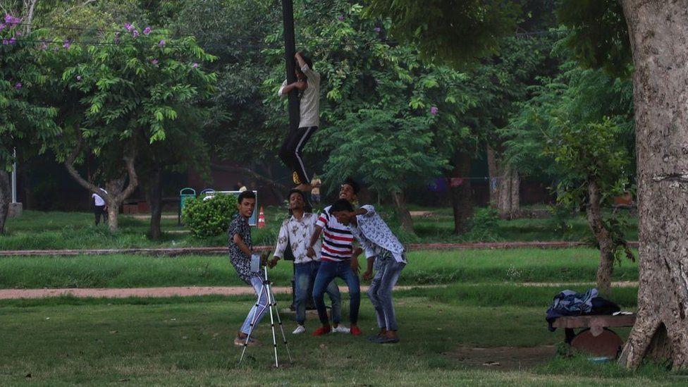 Young boys make videos for TIKTOK in a park in New Delhi