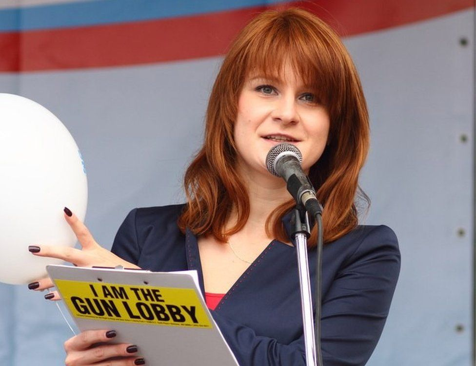 Butina speaks into a microphone while holding a clipboard which says, on its back: I am the gun lobby