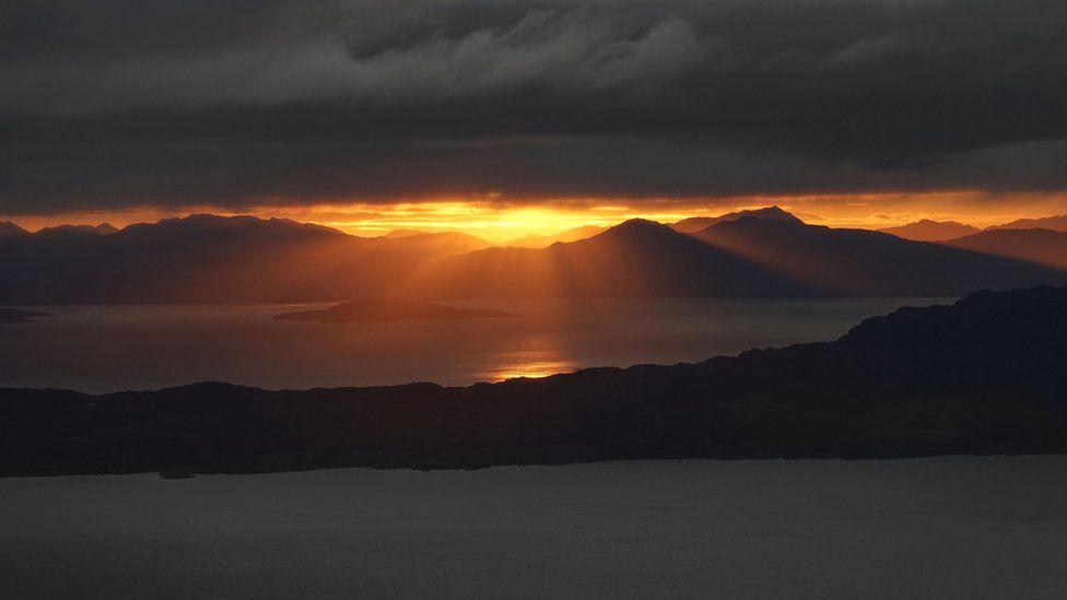 Low sun through mountains