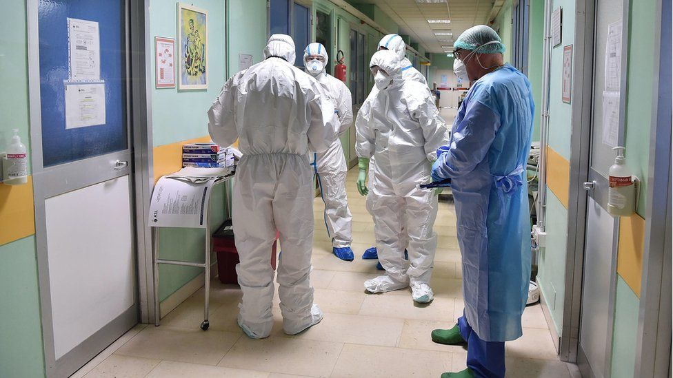 Healthcare professionals wearing protective suits and healthcare masks at work inside the isolation area of the Amedeo di Savoia hospital in Turin, northern Italy