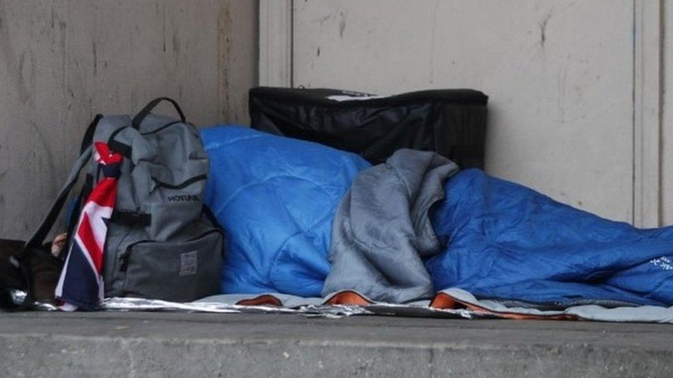Homeless person sleeping rough in a doorway