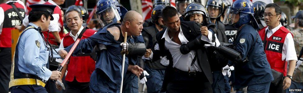 Right-wing activists jostle with riot police officers near Yasukuni Shrine in Tokyo, August 15, 2015