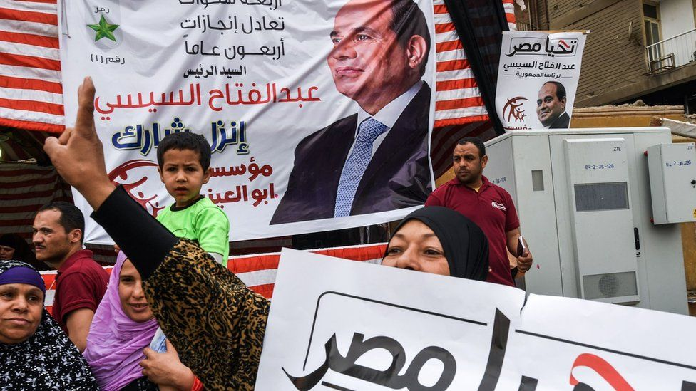 A supporter of Abdul Fattah al-Sisi makes a victory gesture outside a polling station in Giza, Cairo (28 March 2018)