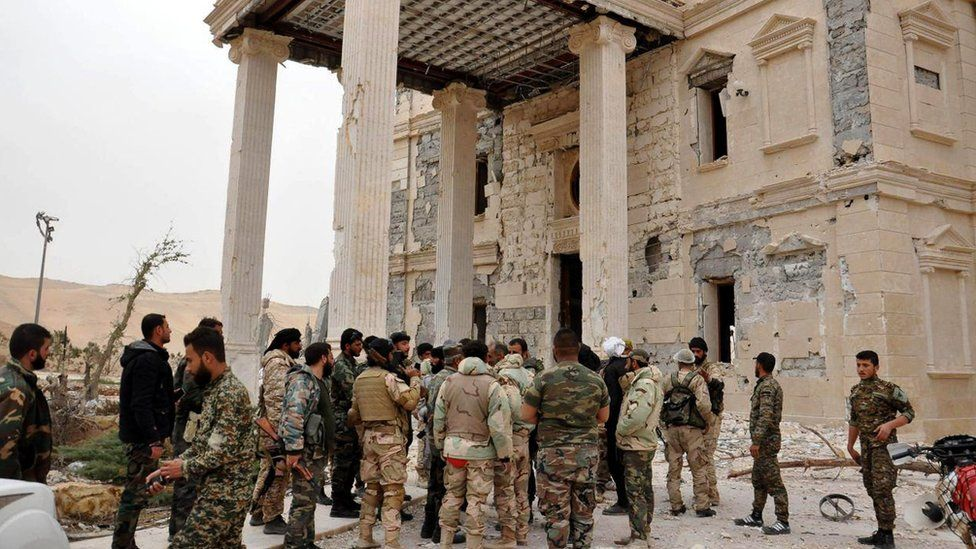 Photo released by official Sana news agency purportedly showing Syrian government soldiers inspecting a damaged palace outside Palmyra (24 March 2016)