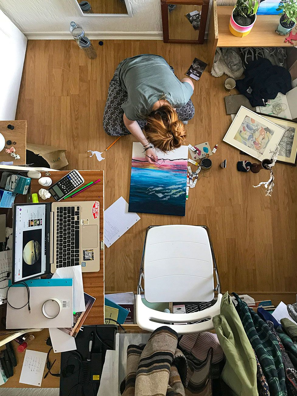 A woman paints a picture in her bedroom
