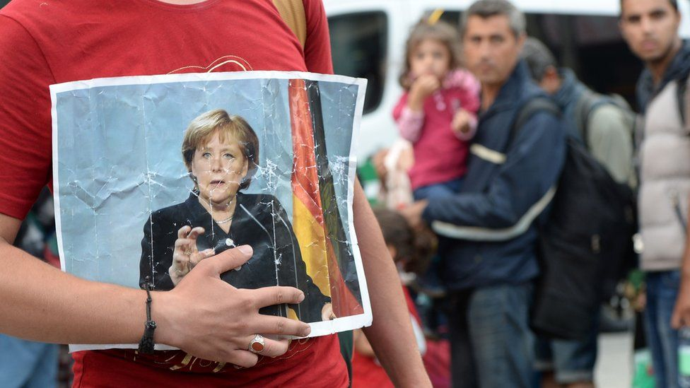 A migrant holds a picture of German Chancellor Angela Merkel after the arrival of refugees at the main train station in Munich, southern Germany, 15 September 2015