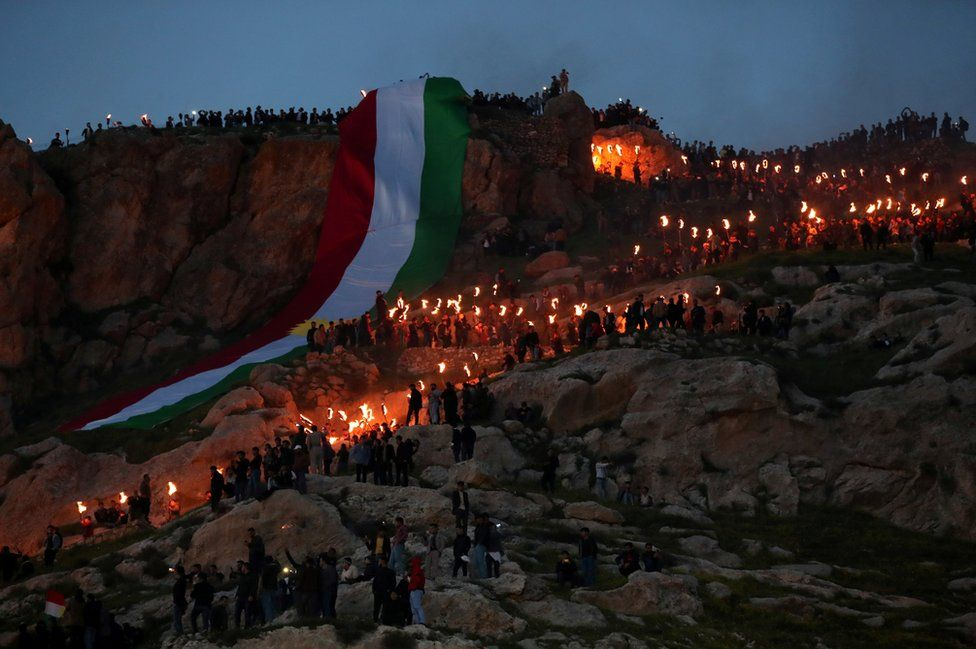 Iraqi Kurdish people carry fire torches up a mountain, as they celebrate Nowruz Day, a festival marking the first day of spring and the new year, in the town of Akra., near Duhok, in Iraqi Kurdistan, Iraq.