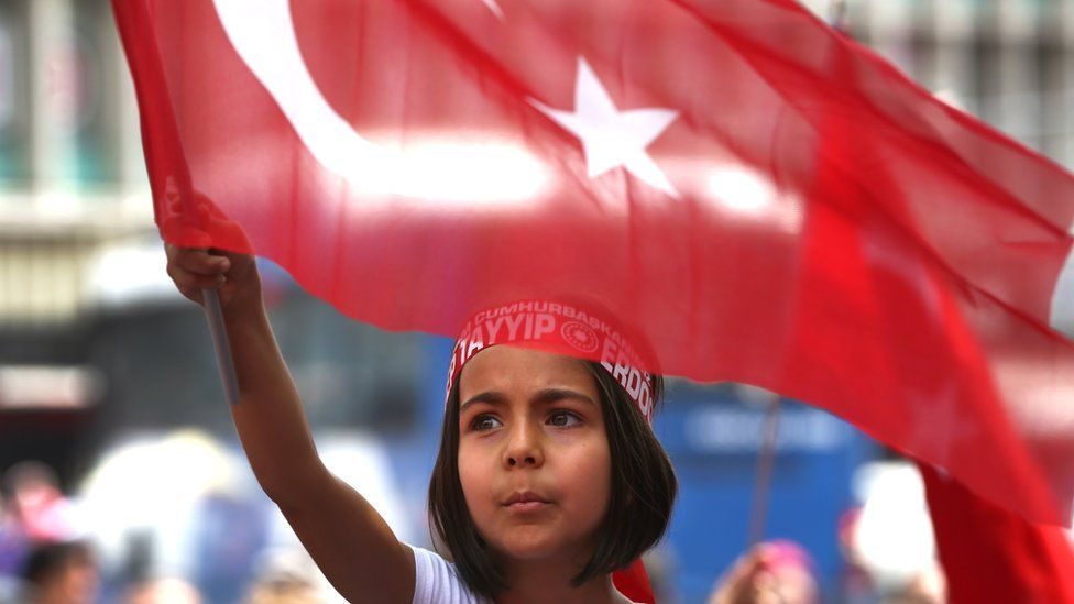 A Turkish girl wearing a headband bearing the name of Turkish president Recep Tayyip Erdogan waves her nation flags during a pro-government demonstration in front of the old parliament building, in Ankara, Turkey (July 20, 2016)