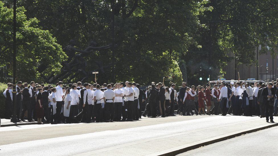 A group of staff members gathered in Hyde Park after they were led from the building