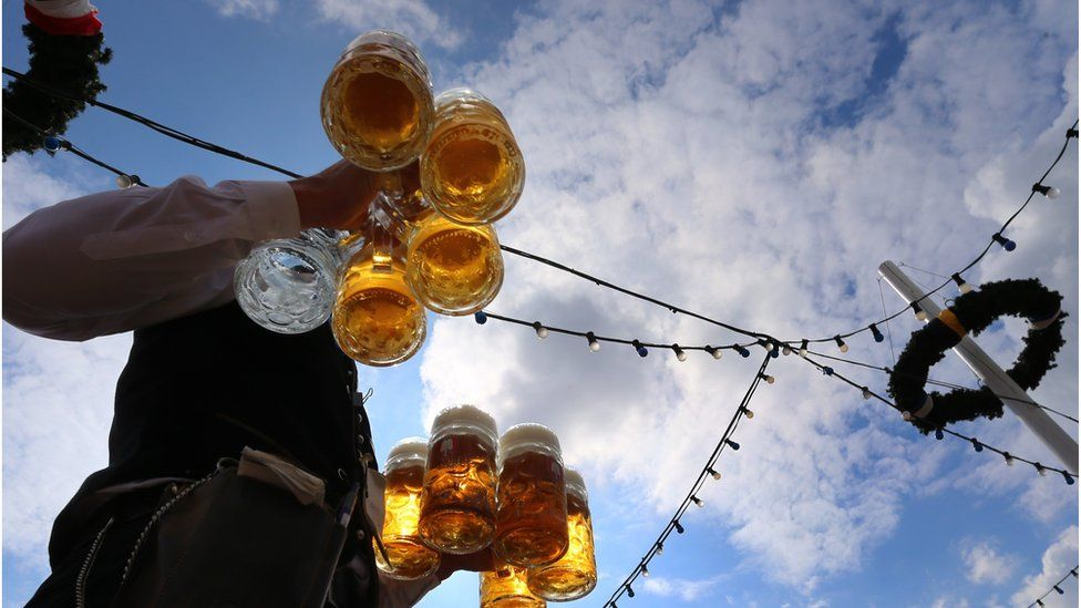 A waiter carries beers at the Theresienwiese fair grounds of the Oktoberfest beer festival in Munich, southern Germany, on September 20, 2015.