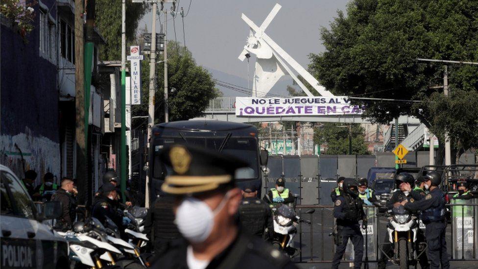 La calle de acceso a una iglesia en Ciudad de México está bloqueada y custodiada por policías.
