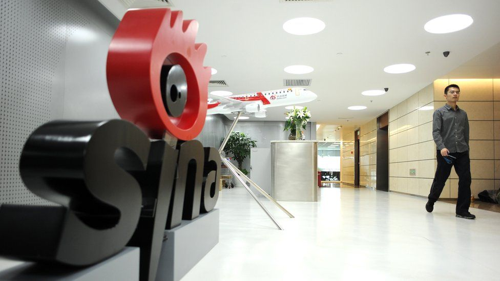 A man walks past the office entrance of Sina in Beijing