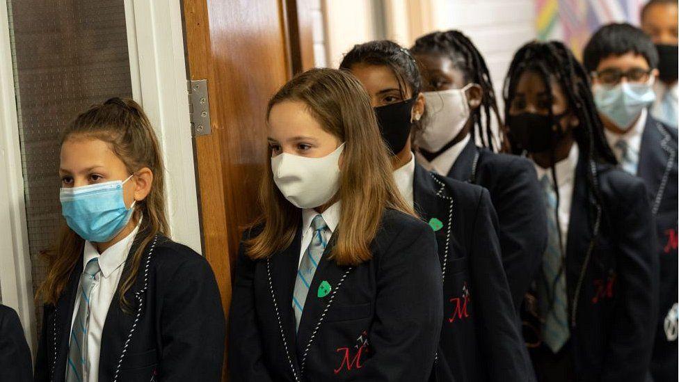 school children queuing wearing masks
