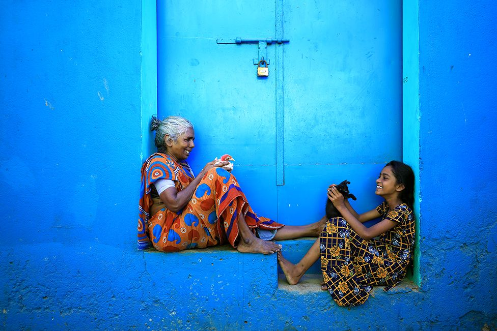 An elderly woman and a girl sit in a blue doorway with a black kitten and a chicken