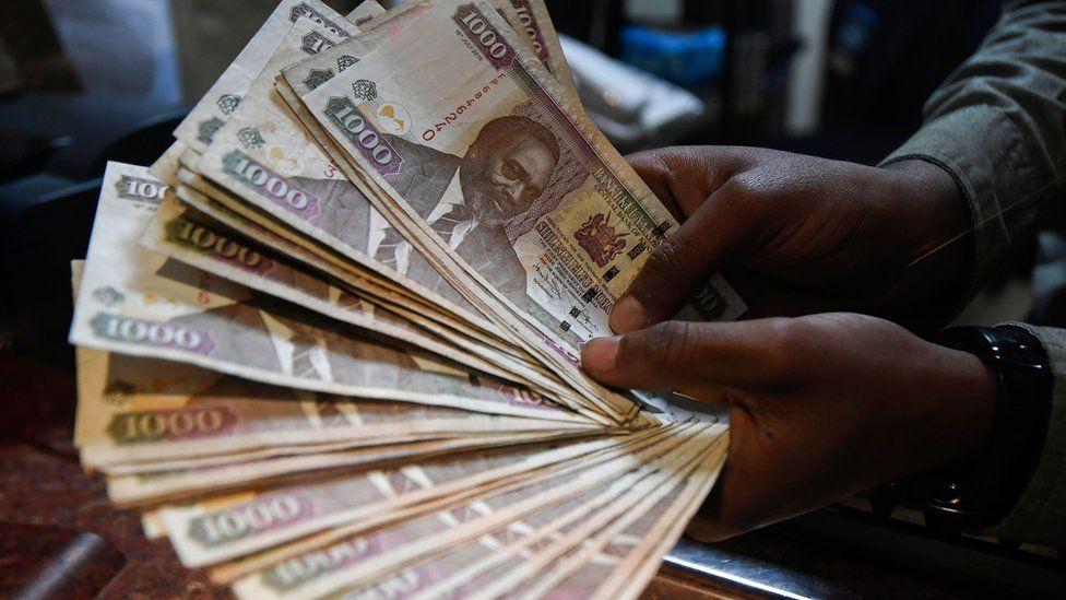 A currency dealer counts Kenyan shillings at a money exchange bureau on September 19, 2018 in the Kenyan capital Nairobi.