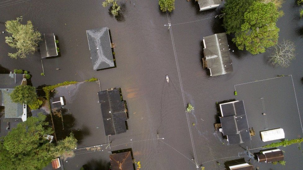 Aerial view of houses, flooding and people paddling in canoes in New Bern