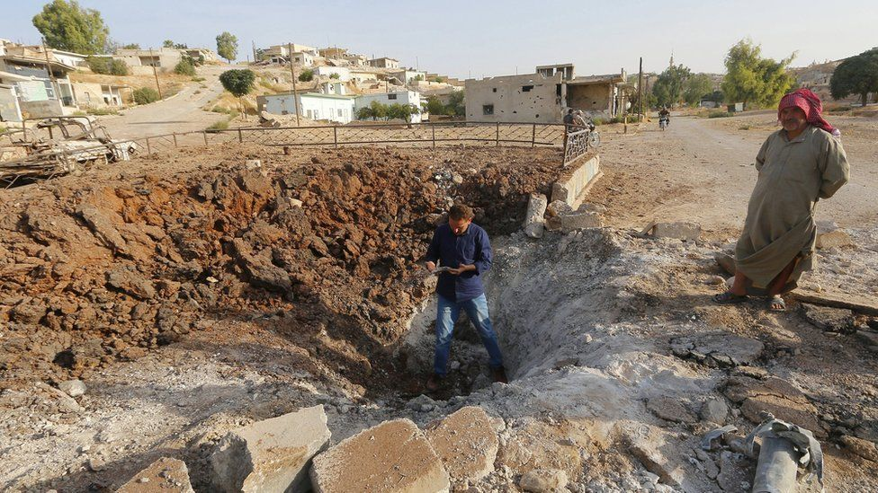 Men stand along a crater caused by what activists said was a Russian air strike in Latamneh city in the northern countryside of Hama