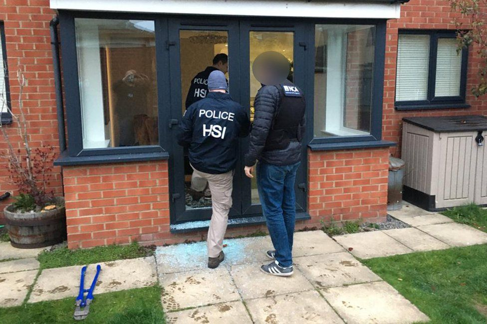 Police entering a property as part of an investigation into a gang selling large quantities of ecstasy around the world on the dark web