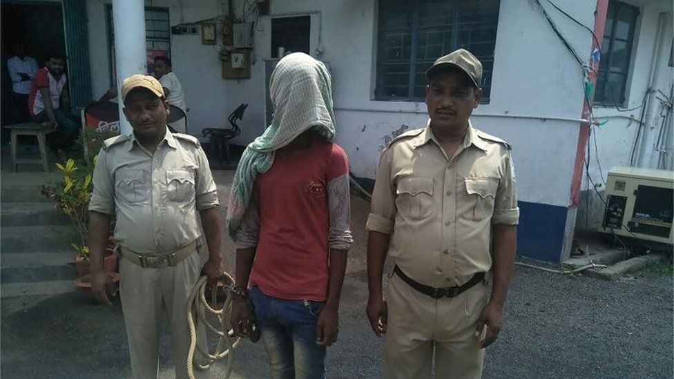 "This photo taken on May 6, 2018 shows an alleged rapist (C) being held by Indian police, in the case of a 17-year-old girl who was raped and set on fire, at Mufasil police station before being sent to judicial custody in Pakur district, in India""s eastern Jharkhand state."