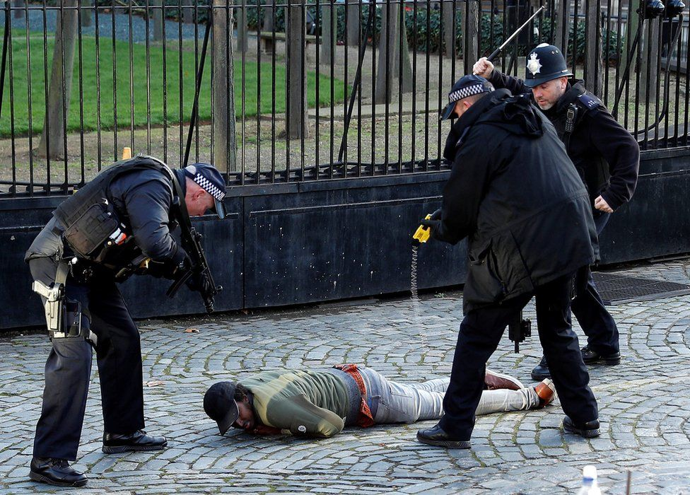 Armed police officer tasers a man