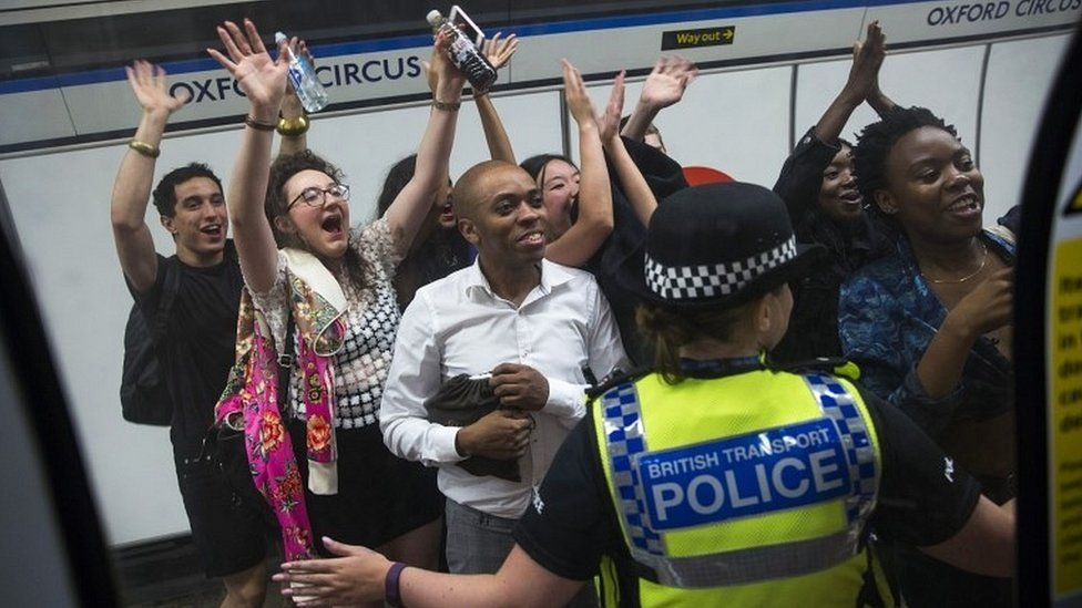 Members of the public wave and cheer as they see London Mayor Sadiq Khan in a tube train carriage