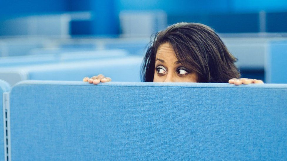 Woman peeping over office divider