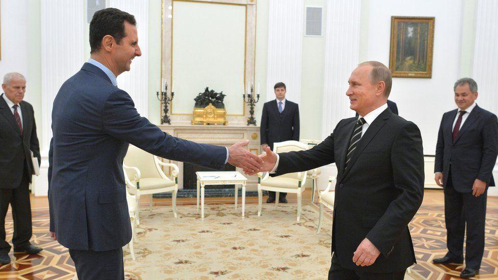 Vladimir Putin shakes hands with Syrian President Bashar Assad in the Kremlin in Moscow