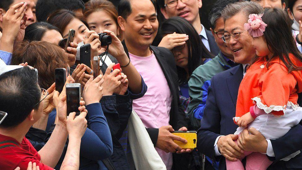 Ông Moon Jae-in bế cháu khi tiếp xúc cử tri lúc tranh cử tổng thống Hàn Quốc