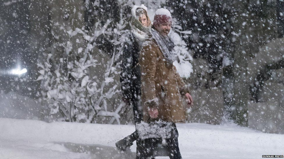 This is a photo of a couple walking in the snow.