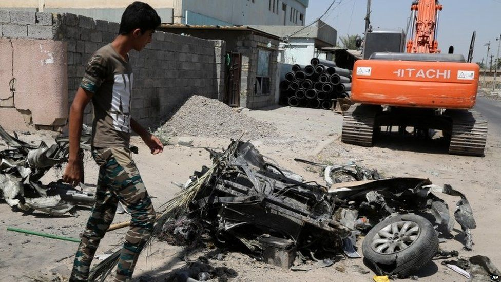 A man inspects the scene of an explosion in a busy commercial area in Baghdad (13 July)